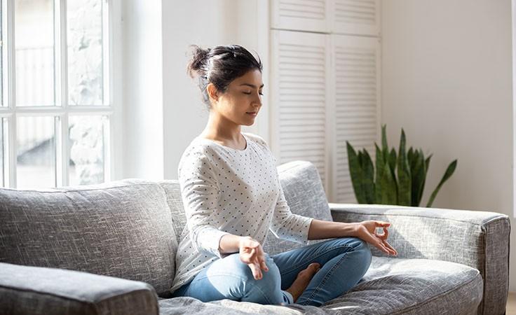 Meditation: Frau meditiert auf der Couch