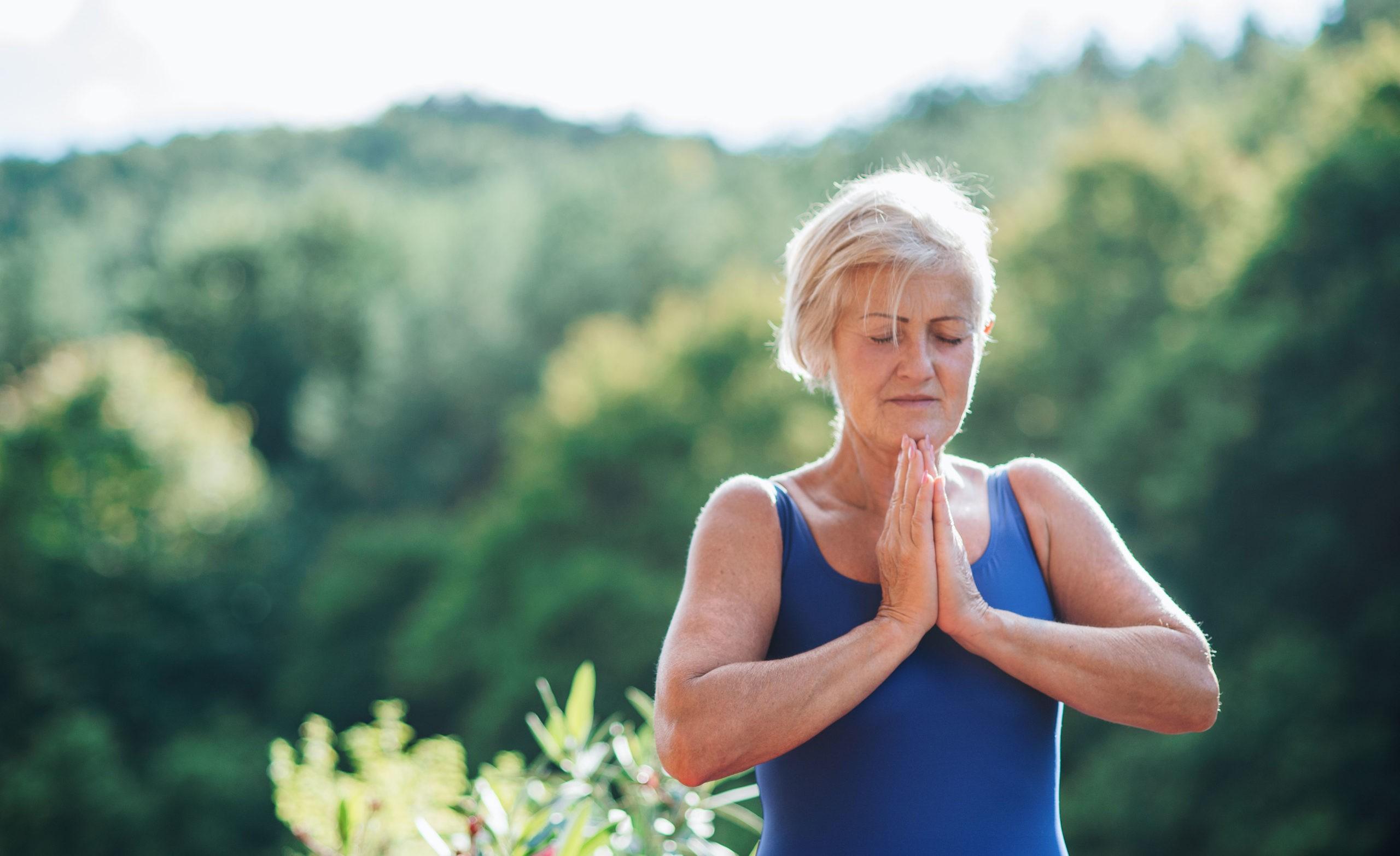 Ältere Frau meditiert in der Natur