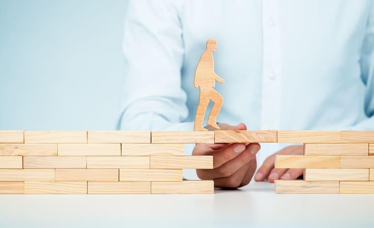 Holzfigur bekommt Hilfe beim Ueberqueren einer Bruecke