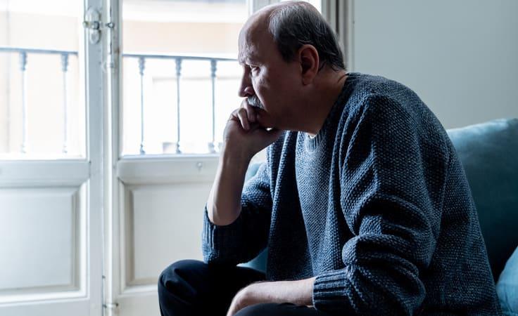 Aelterer Mann schaut traurig aus dem Fenster