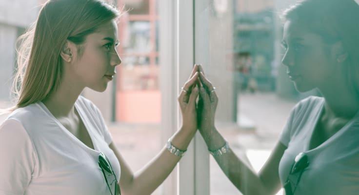 Abbild einer jungen Frau reflektiert im Schaufenster